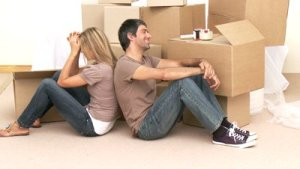 stock-footage-footage-in-high-definition-of-tired-couple-sitting-on-floor-after-moving-house-with-boxes-around